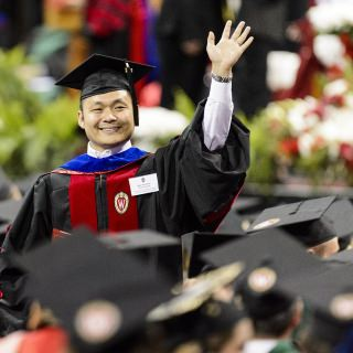 Won Hwa Kim, a doctoral graduate in computer sciences, waves to family.