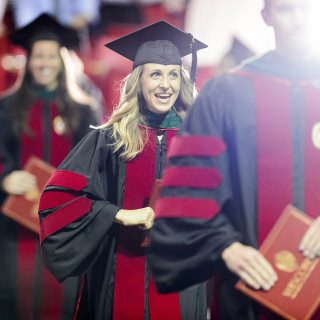 Graduates walk with their diploma cases during UW-Madison's spring commencement ceremony at the Kohl Center.