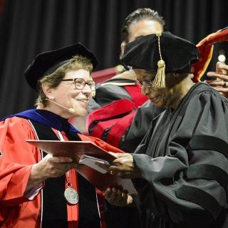 Chancellor Rebecca Blank presents an honorary degree to sociologist Cora Marrett (right).