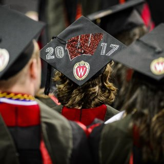 A graduate displays a decorated graduation cap.