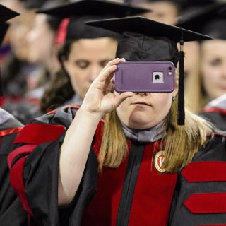 A graduate captures the moment with her cellphone camera during UW-Madison's spring commencement ceremony at the Kohl Center.