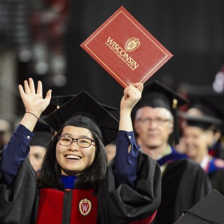 A graduate holds up her diploma cover to show family.
