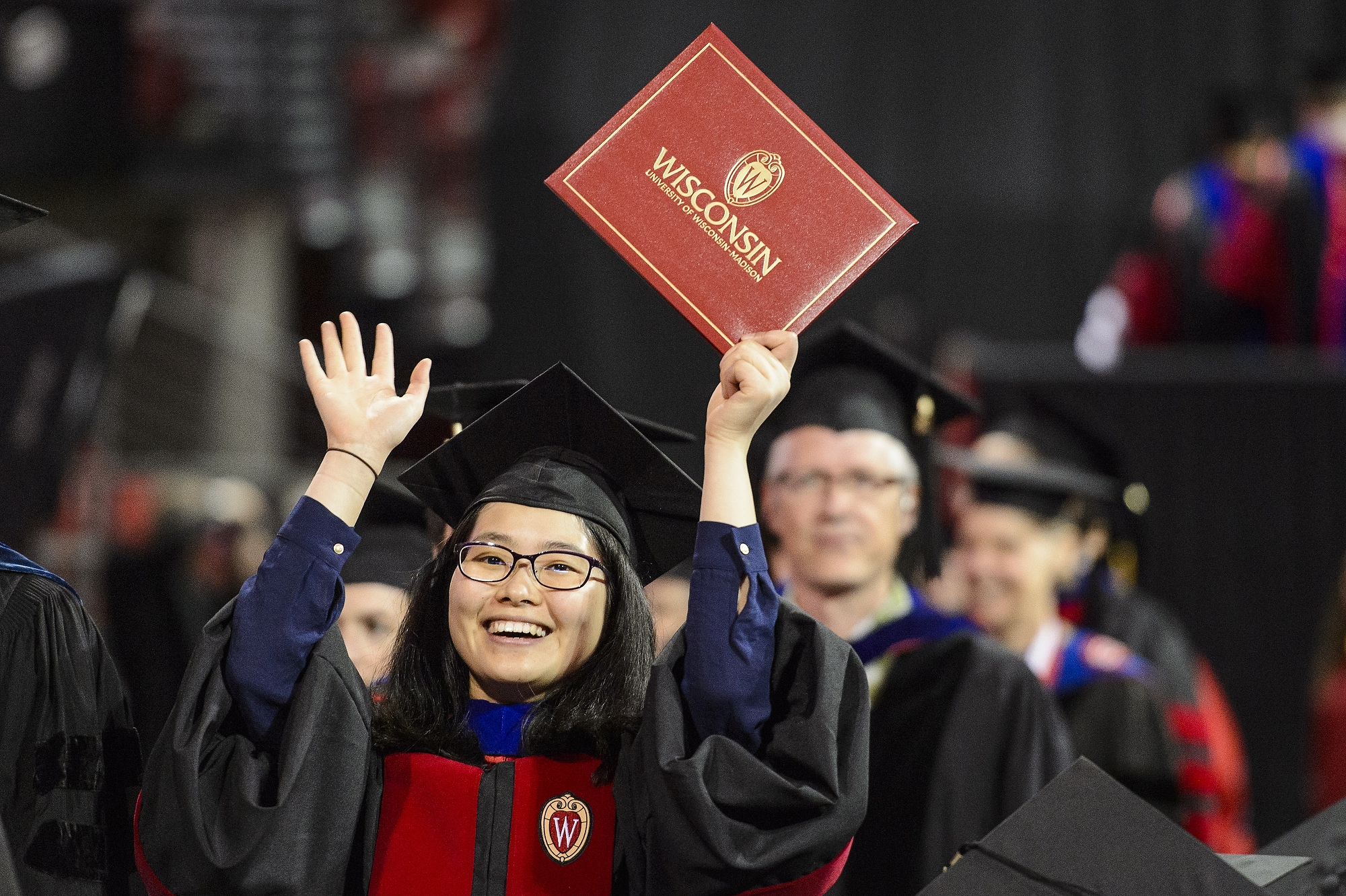 A graduate holds up her diploma cover to show family during UW–Madison's spring commencement ceremony at the Kohl Center at the University of Wisconsin–Madison on May 12, 2017. The indoor graduation was attended by approximately 830 doctoral, MFA and medical student degree candidates, plus their guests. (Photo by Bryce Richter / UW–Madison)