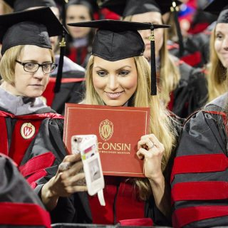 A graduate takes a selfie with her diploma cover during UW-Madison's spring commencement.