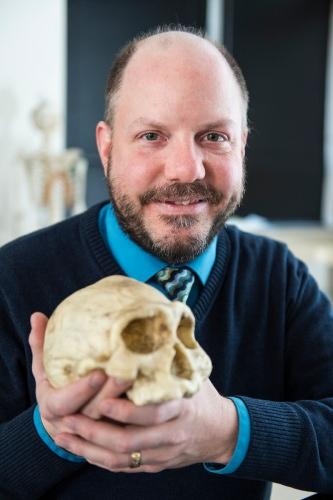 Photo: John Hawks holding skull