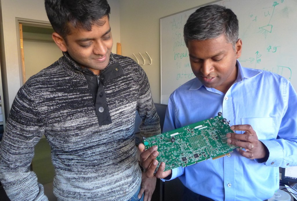 Graduate student Vijay Thiruvengadam, left, and Karu Sankaralingam, an associate professor of computer science at the University of Wisconsin–Madison, with a prototype board used to explore a new, streamlined approach specifically designed to improve performance and reduce electricity wastage at data centers.