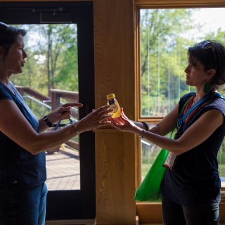 Wisconsin Idea Seminar Director Catherine Reiland (right) presents honey collected around Madison to Marcy West (left), executive director of the Kickapoo Valley Reserve. Local gifts produced in Madison were a way for seminar participants to show appreciation for presenters who shared their own experiences.