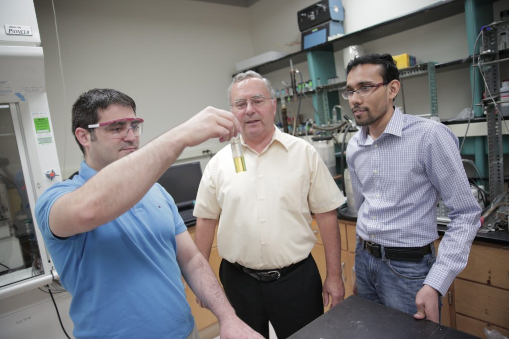 UW–Madison engineers, from left, David Martin Alonso, James Dumesic and Ali Hussain Motagamwala, examine a vial of furfural, one of a group of valuable products the researchers can now create as part of the biofuel refining process.