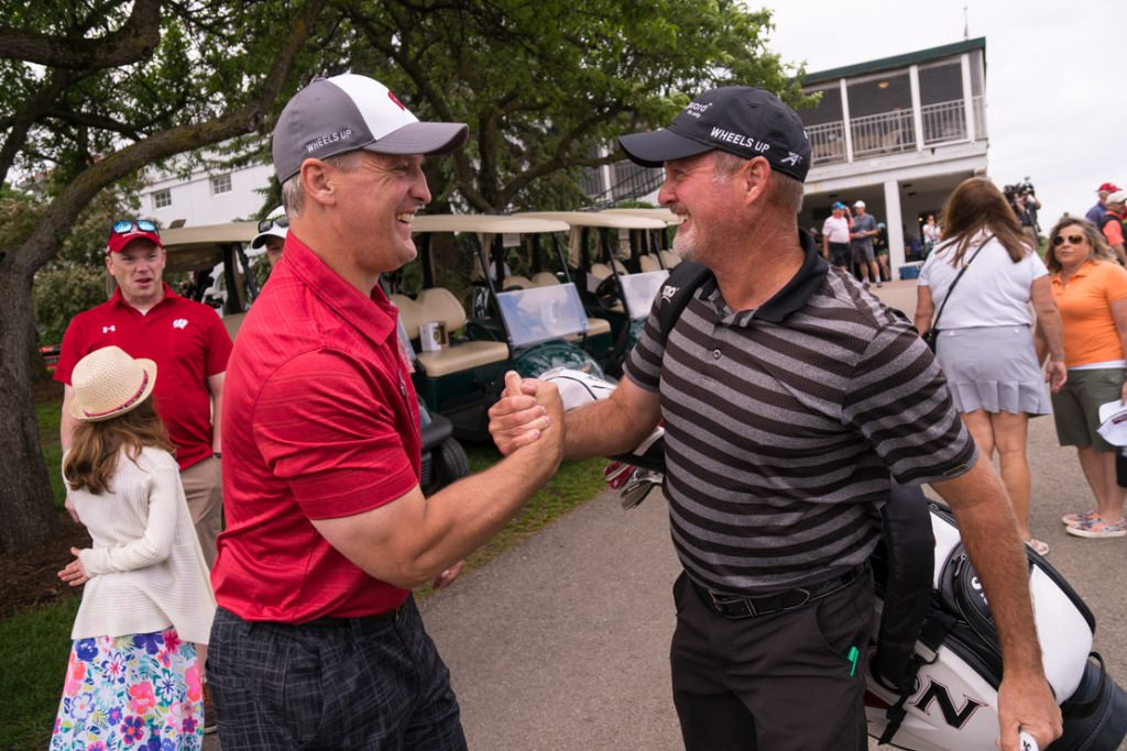 Pro golfer Jerry Kelly, right, gives a hearty handshake to Mark Osiecke, assistent men's hockey coach.