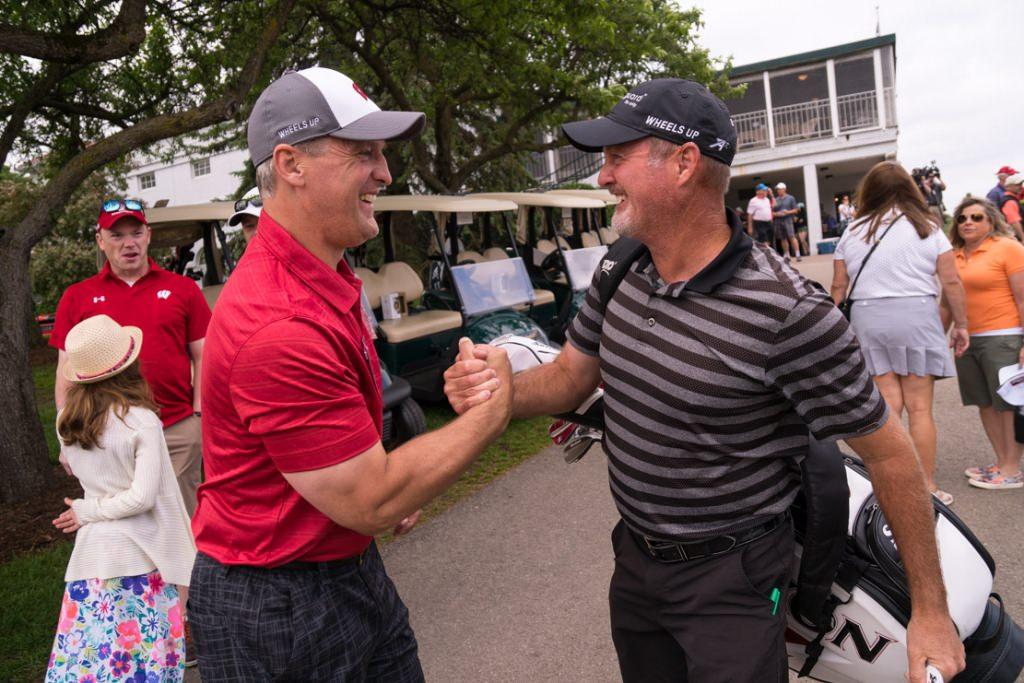 Pro golfer Jerry Kelly, right, gives a hearty handshake to Mark Osiecke, assistent men's hockey coach.