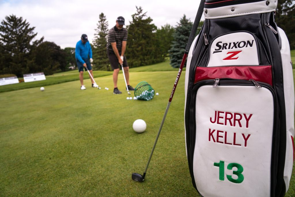 Pro golfer Jerry Kelly putts; Billy Andrade is behind him.