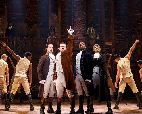 """Photo: """"Hamilton"""" cast members in costume on stage"""