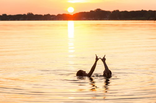 Having stayed up all night, undergraduates Loran Zweifelhofer and Willis Perley form a W hand sign as they greet the morning sunrise over Lake Mendota with a swim from the Goodspeed Family Pier near the Memorial Union Terrace at the University of Wisconsin–Madison on June 19, 2015. The two friends met during their freshman year and are now seniors. (Photo by Jeff Miller/UW-Madison)