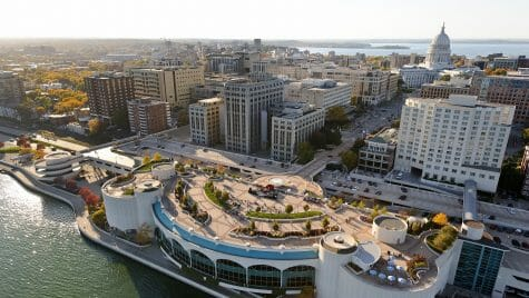 Counter clockwise from lower left, Lake Monona, the Monona Terrace Community and Convention Center, and Wisconsin State Capitol are pictured in an aerial view of the downtown Madison skyline during an autumn sunset on Oct. 5, 2011. In the background, right of center, is the University of Wisconsin-Madison campus, Picnic Point and Lake Mendota. The photograph was made from a helicopter looking west. (Photo by Jeff Miller/UW-Madison)
