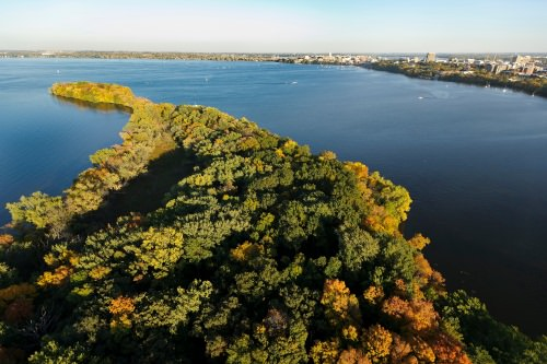 Picnic Point and Lake Mendota are pictured in an aerial view of the University of Wisconsin–Madison campus during an autumn sunset on Oct. 5, 2011. On the horizon is the downtown Madison skyline, right of center, and central UW–Madison campus, at far right. The photograph was made from a helicopter looking southeast. (Photo by Jeff Miller/UW-Madison)