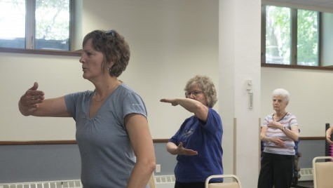 "Diane Brose, left, leads a tai chi class in La Crosse. Phyllis Branson, right, says, ""I'm very aware of being able to maintain my balance."" Chairs are used to guard against falls in the class."
