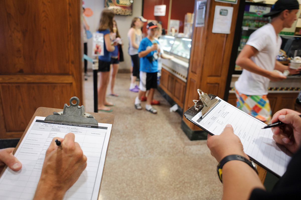 Photo: Two people writing on clipboards by ice cream counter