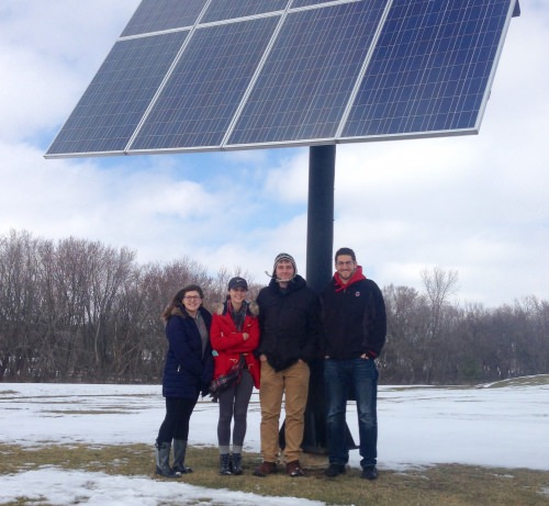 Students from capstone class pose with a solar panel outside the Waterloo, Wisconsin utilities building: from left: Lisa Walsh, Bailey Zak, Jim Costello-Mikecz and Alex Bristol. Not pictured was James Zavoral.