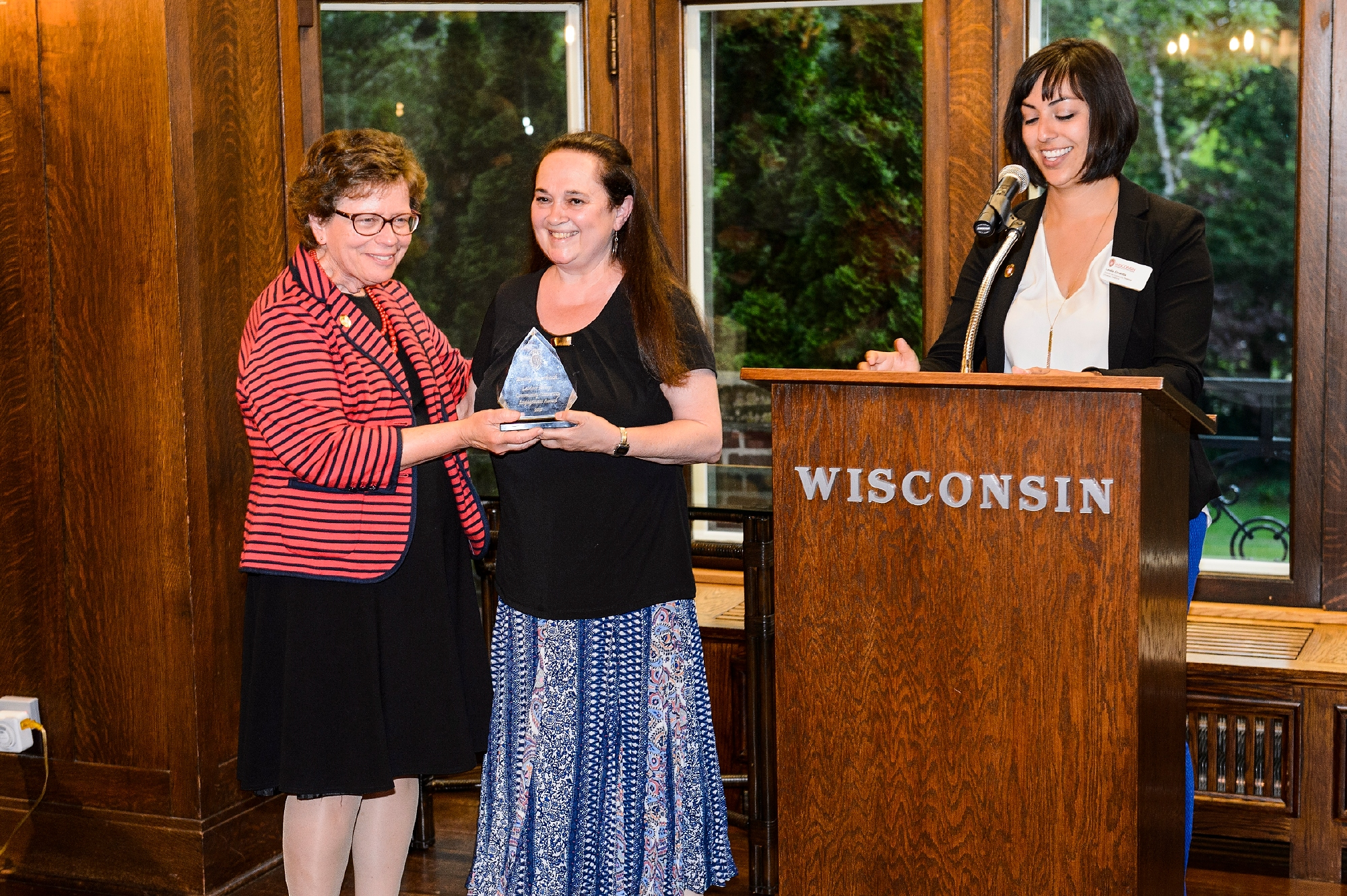 Emily Auerbach, professor of English at UW–Madison, receives the 2017 LaMarr Billups Community-University Engagement Award during a 2017 Community-University Partnership Award event at Olin House, the Chancellor's residence at the University of Wisconsin–Madison on June 28, 2017. Presenting the awards are UW–Madison Chancellor Rebecca Blank and Leslie Orrantia, UW–Madison director of community relations. (Photo by Jeff Miller / UW–Madison)