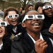 Students watch a solar eclipse through solar glasses, which allow safe viewing of the sun.