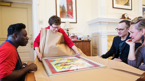 UW-Madison Chancellor Rebecca Blank receives a gift of artwork from alumnus and local artist Michael Ward, left, on Aug. 16.