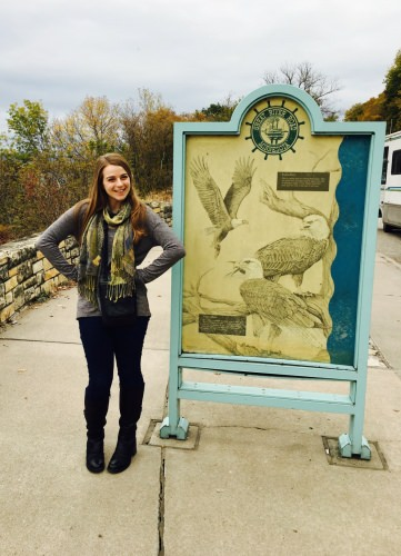 Photo: Olivia Sanderfoot posing in front of sign with pictures of Eagles