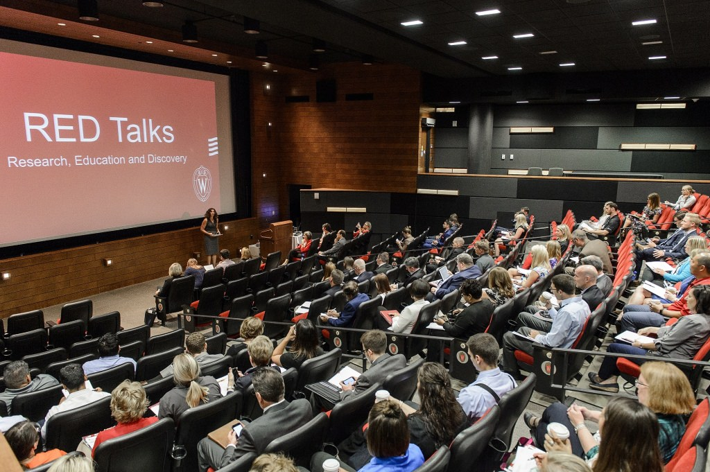 Photo: Auditorium with people watching unidentified person giving RED Talk