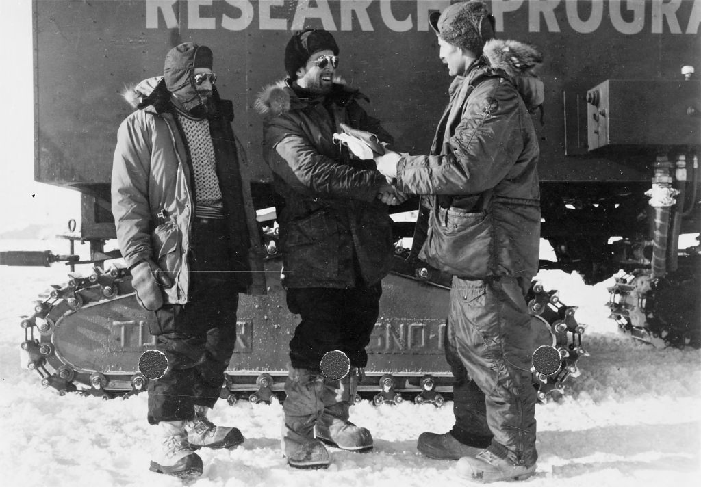 Photo: Charles Bentley shaking hands with unidentified man in front of Antarctic research vehicle