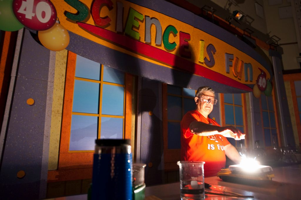 Photo: Bassam Shakhashiri presenting science show in dark room illuminated from lab bench