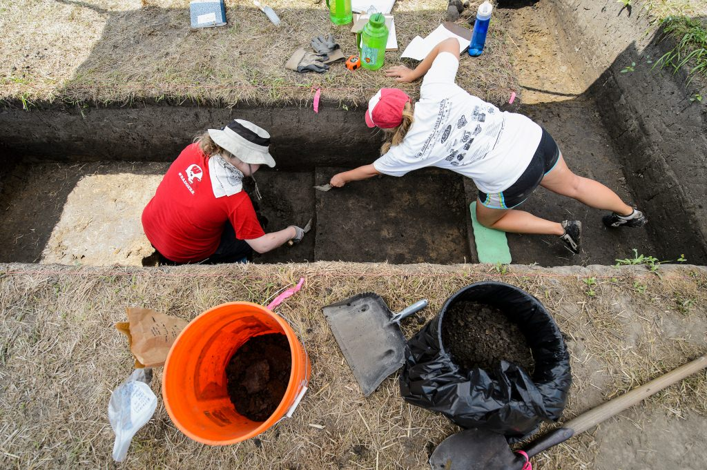 Photo: People digging with trowels in archaeological site