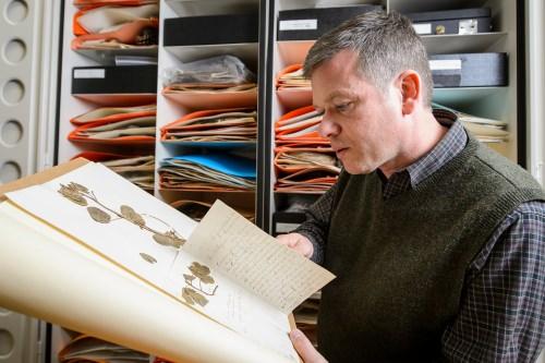 Photo: Ken Cameron looking at book of plant samples