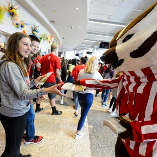 Bucky Badger helps distribute complimentary copies of