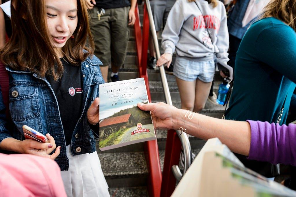 Photo: Volunteer handing book to student