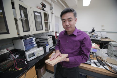 Photo: Xudong Wang holding piece of wood used in energy-harvesting flooring