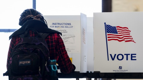 Photo: Person filling out ballot in polling booth