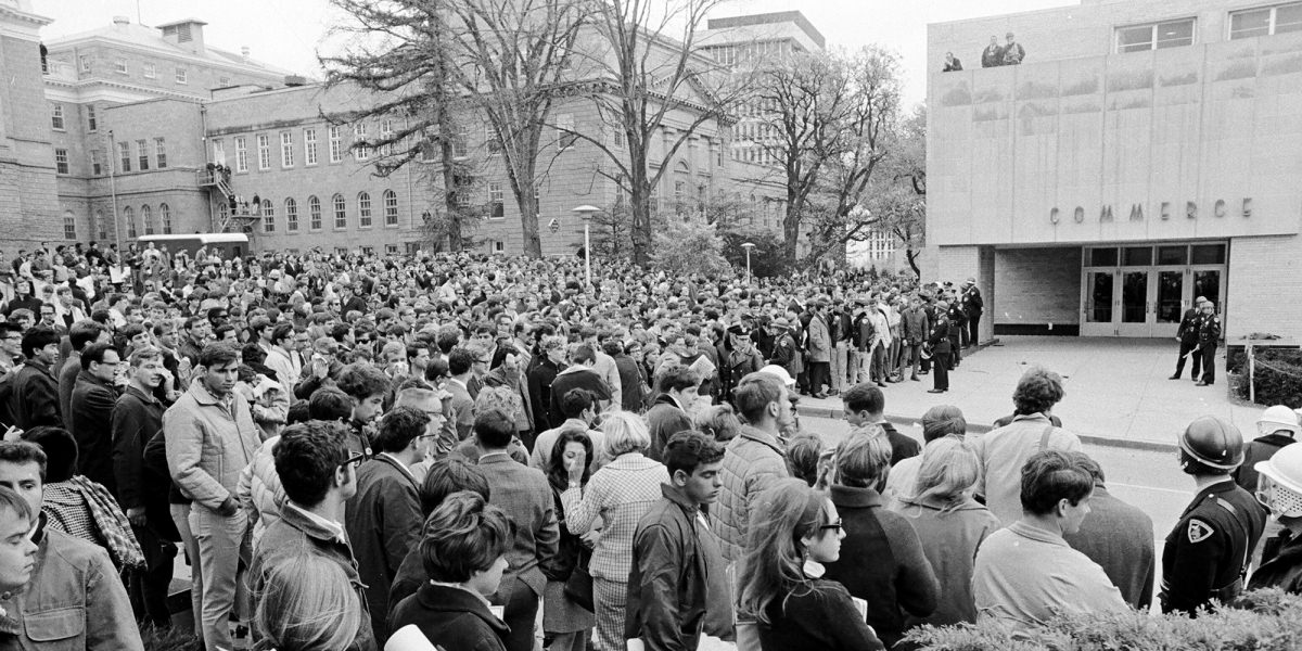 Students gather outside Commerce Hall, guarded by policemen, on October 18, 1967, during the Dow Chemical protests.