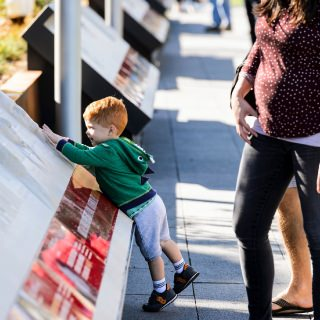 Graham Kourliouros, 2, takes a hands-on approach as people look at displays while walking through Alumni Park.