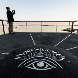 Karl Olson, university staff with the School of Veterinary Medicine, takes in a dawn view of Lake Mendota from Alumni Park's Progress Point at the University of Wisconsin-Madison during the autumn morning of Oct. 8, 2017. In the foreground is a backlit logo of the university's Numen Lumen seal. The newly-opened park, part of the Wisconsin Alumni Association (WAA), is located between the Memorial Union and Red Gym (Armory and Gymnasium) overlooking the Lake Mendota shoreline.