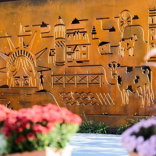 Cut into rusted-steel, backlit and iconic graphics of the Badger Pride Wall – including the Statue of Liberty, cows and farm land – are part of the many informational displays featured at Alumni Park.