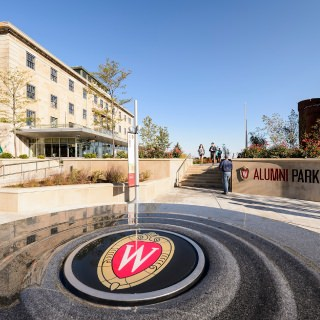 A W crest adorns the center of a water fountain at the entrance to Alumni Park.
