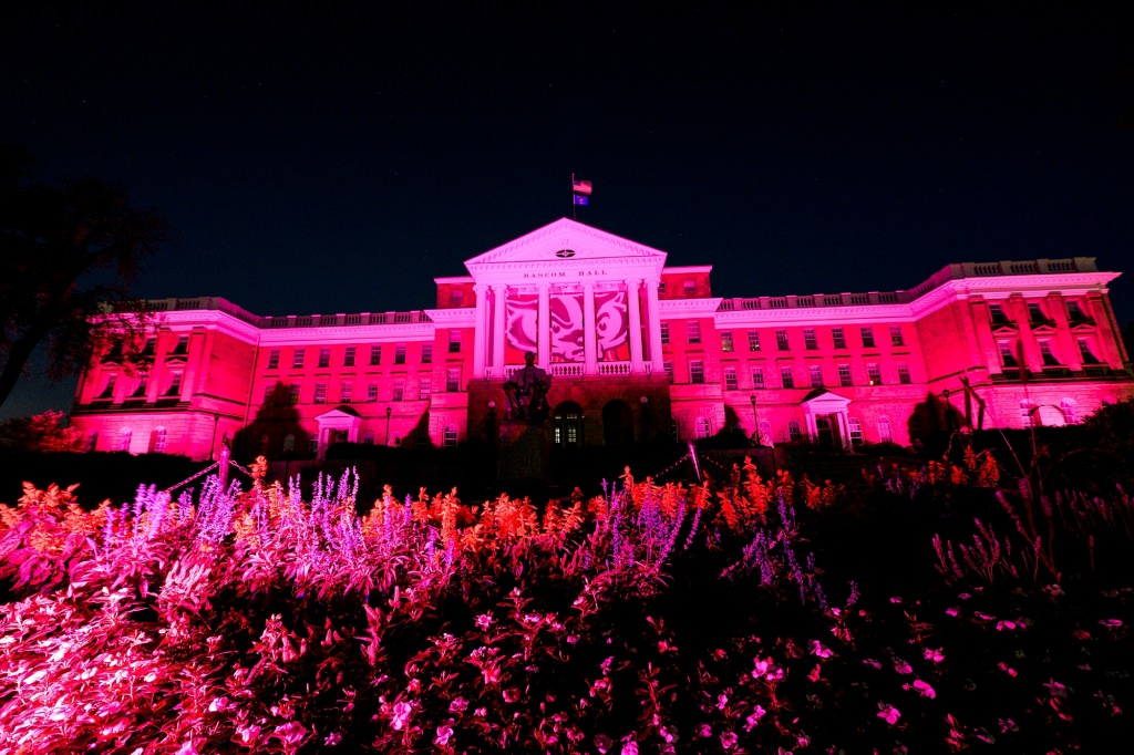 In honor of Breast Cancer Awareness Month, pink-colored accent lighting illuminates the exterior of Bascom Hall and terrace plantings surrounding the Abraham Lincoln statue at the University of Wisconsin-Madison as dawn brightens the night sky on Oct. 20, 2017. Hanging between the building's column is a graphic banner of UW-Madison mascot Bucky Badger. (Photo by Jeff Miller / UW-Madison)