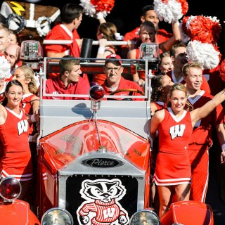 Members of the UW Spirit Squad and the Bucky Wagon make their way down the tunnel just before the start of the UW Homecoming football game.