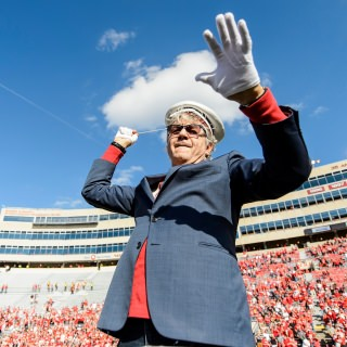 UW-Madison alum Steve Miller, of the Steve Miller Band, conducts the UW Marching Band during the fifth quarter celebration.