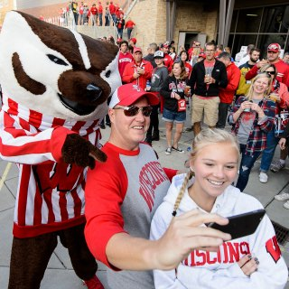 Badger fans pose with UW mascot Bucky Badger for a selfie during the Badger Bash at Union South before the UW Homecoming football game.