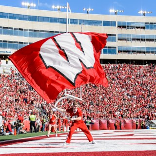 A member of the UW Spirit Squad waves a giant W flag after the Badgers score a touchdown.