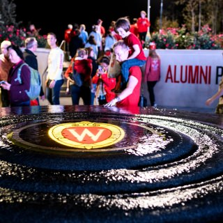 A water fountain with illuminated W Crest flows at the recently-opened Alumni Park during the UW Homecoming Block Party.