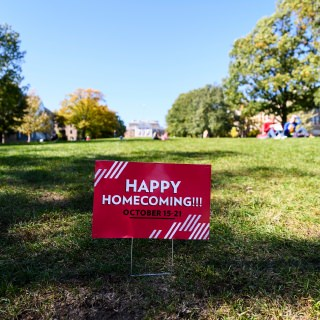 An advertising sign promoting a Happy Homecoming is posted at the base of Bascom Hill.