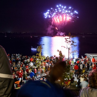 UW alumni and members of the Madison community take in a fireworks display over Lake Mendota.