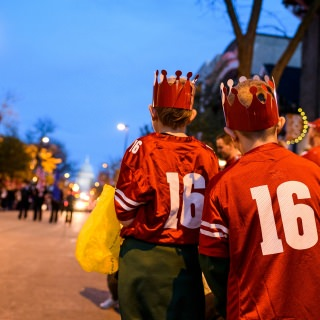 Children anxiously await the potential for receiving candy as spirited students dance and parade floats travel down State Street during the University of Wisconsin-Madison's Homecoming Parade.
