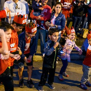 Children anxiously await the potential for receiving candy as spirited students dance and parade floats travel down State Street.